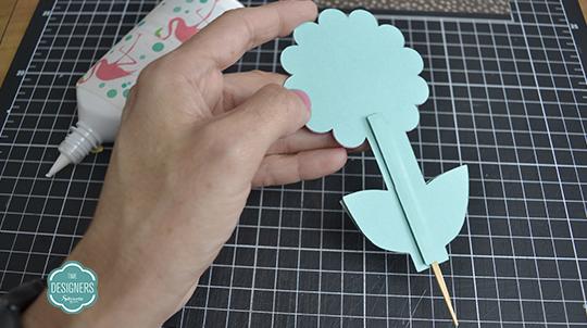 Cubra o palito colando tira de papel verde (o mesmo usado na base da flor)