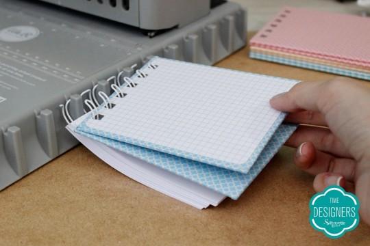Encaixe o wire-o na lateral da The Cinch. Em seguida, encaixe ante capa, páginas e capa no wire-o