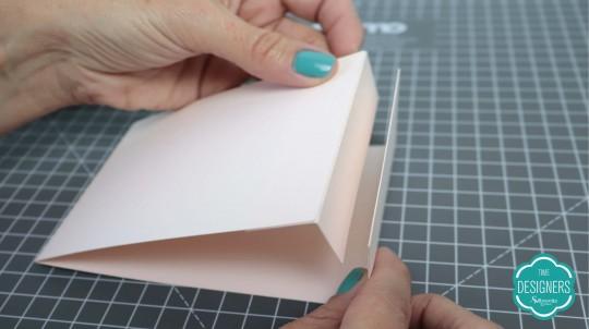 Cole a tira menor nas duas extremidades papel, formando um apoio, e cole-o em cima do porta-retrato